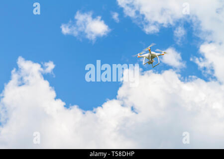 White drone quad copter with high resolution digital camera flying in the blue sky - Stock Photo