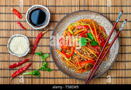 Starch (rice, potato) noodles with vegetables - bell peppers, carrots, cucumber, sesame seeds, cilantro and soy sauce. Vegetarian dish. A delicious lu - Stock Photo