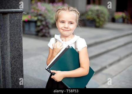 Happy little schoolgirl with book going back to school outdoor - Stock Photo