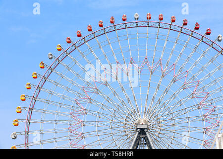 Ferris Wheel near to Tempozan Harbor village, Osaka, Japan. On blue sky background - Stock Photo