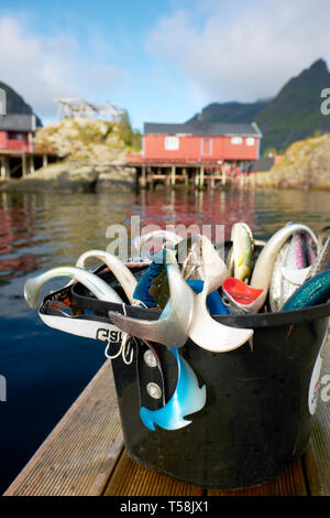 A bucket of tourist sea fishing lures and Rorbu Norwegian traditional fisherman houses in the fishing village of Å in the Lofoten islands Norway - Stock Photo