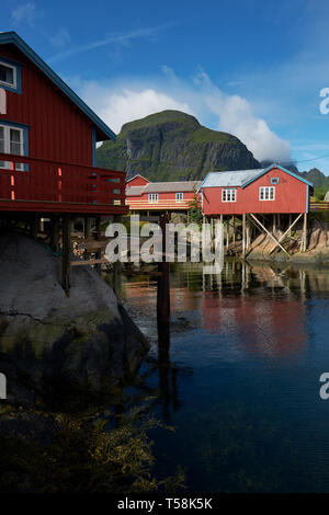 The red Rorbu Norwegian traditional fisherman houses built on wooden stilts in the fishing village of Å on Moskenesøya in the Lofoten islands Norway - Stock Photo