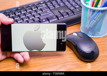 PIATRA NEAMT, ROMANIA - APRIL 13, 2019: Hand holds the new Huawei flagship, P30 Pro, with Apple Inc. on the screen, office background. - Stock Photo