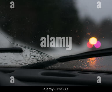 Stormy drive in car with wet windshield wipers on dashboard - Stock Photo