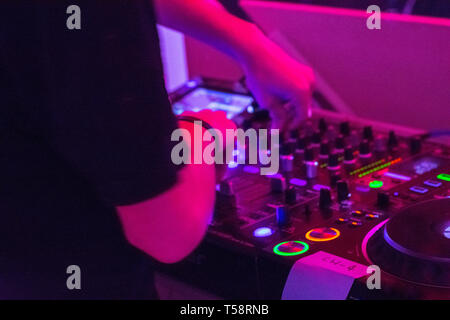 DJ on turntables playing electronic music in dark nightclub in the city - Stock Photo