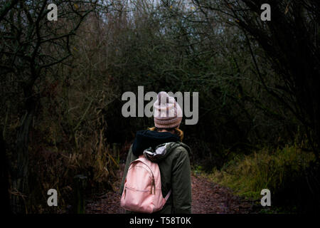 Girl in beanie and backpack walking on path through dark spooky woods at night - Stock Photo