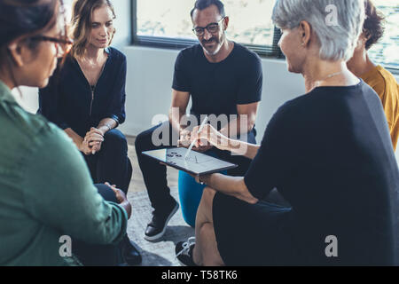 Multi-ethnic group of people sitting together having a group discussion. Business people having a meeting on new working strategies.