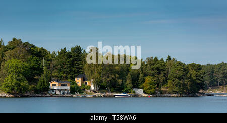 Bright yellow-walled houses on Soderon Island overlooking the Baltic Sea in the Stockholm Archipelago - Stock Photo