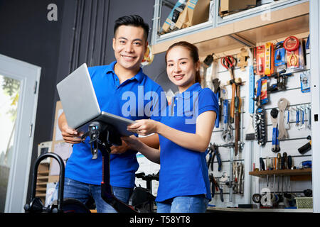 Couple in a bicycle repair shop - Stock Photo