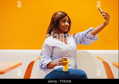 African woman sitting on cafe against orange wall with pineapple juice in hands and making selfie. - Stock Photo