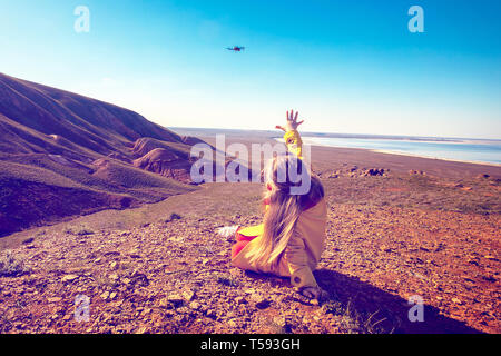 The little girl look at the drone. Natural landscape. - Stock Photo