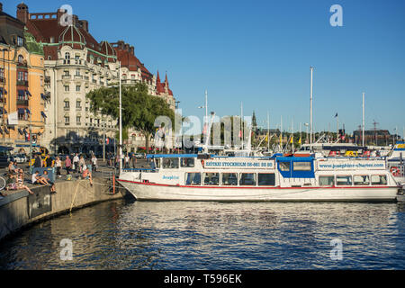 People enjoying the late afternoon sun by Nibroviken bay flanked by  Hotel Esplanade, Hotel Diplomat and the grand buildings of Strandvägen - Stock Photo