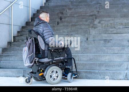 young disabled man in a electric wheelchair in front of stairs - Stock Photo