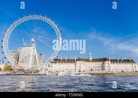 England London - April 20, 2019: London Eye near County Hall in summer view from Thame river boat cruise - Stock Photo