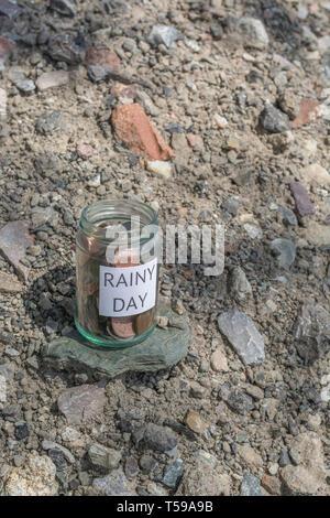 Money jar / rainy day savings jar outdoors in sunshine. Metaphor personal savings, saving money, retirement savings, saving for retirement, saving pot