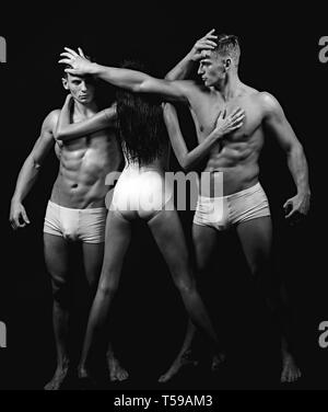 Twins men with muscular body and girl coach. Gymnastic school and energy. Circus gymnasts at pilates or yoga training. Fitness and dieting - Stock Photo