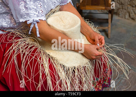 Woman weaving a Panama hat or brimmed straw hat from Toquilla palm fibers. The technique is on the Unesco Intangible Cultural list of Cuenca, Ecuador. - Stock Photo