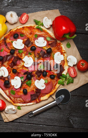 Hot italian pizza on dark wooden table with ingredients and cutter - Stock Photo