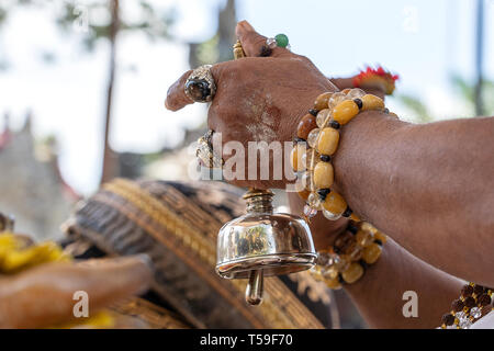 The hands of the priest during the Bade cremation ceremony on central street in Ubud, Island Bali, Indonesia . Close up - Stock Photo