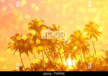 Warm orange sunrise on tropical beach with sun rays through palm trees silhouettes and golden shiny bokeh double exposure effect - Stock Photo