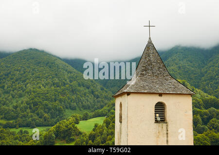Parish Church of Saint Martin bell tower with Aspe countryside with forests and pastures in the background (Aydius, CC Vallée Aspe, Aquitaine, France) - Stock Photo