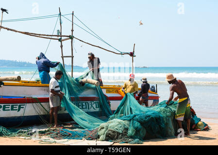 WELIGAMA, SRI LANKA - MARCH 3, 2016: Group local of fishermens reviewing and folding fishing nets near the traditional wooden boat on the ocean beach  - Stock Photo