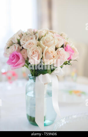 Beautiful wedding bouquet of delicate beige roses stands on the table - Stock Photo