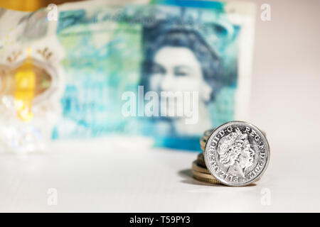 A five pence coin with the image of Elizabeth II over a blurred five pounds from UK.