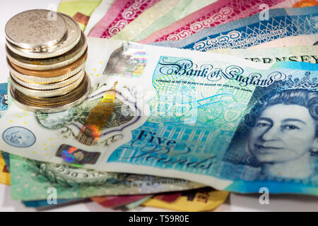 A five pound new polymer banknote from UK with a pile of coins, focus on the bank of england phrase. - Stock Photo