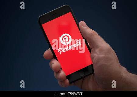 A man looks at his iPhone which displays the Pinterest logo (Editorial use only). - Stock Photo