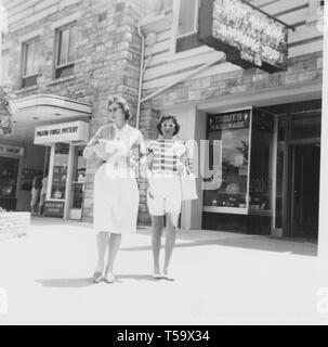 Two ladies enjoy shopping on their Smoky Mountain vacation in Pigeon Forge circa 1960. - Stock Photo