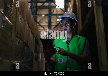 Young Asian male warehouse worker using a digital tablet inside warehouse to check inventory and stock management in factory - Stock Photo