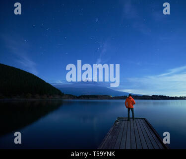 Man looking at Mount Fuji and starry night sky, lake Tanuki, Shizuoka - Stock Photo