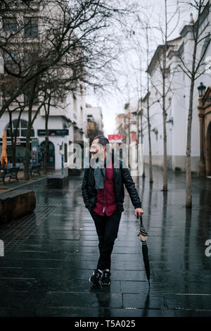 attractive man holding an umbrella while standing on the street - Stock Photo