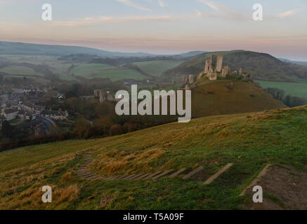Early morning light and mist falls over Corfe village and Castle from east hill with steps in the foreground Dorset - Stock Photo