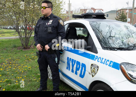 Portrait of a Chinese American police office on duty at a cricket tournament in Baisley Pond Park in Jamaica, Queens, New York City. - Stock Photo