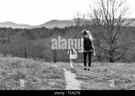 Blue Ridge Mountains in the background, a mother and two young daughters walk on a trail at the Biltmore Estate in Asheville, NC, USA - Stock Photo