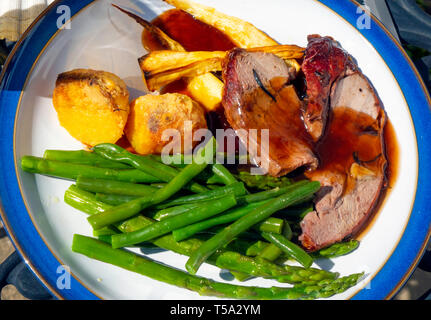 Easter Day English lunch  dinner meal roast lamb roast potatoes green beans parsnips and red wine gravy on a blue edged white plate on  outdoor table - Stock Photo