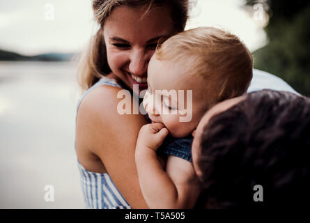 A young family with a toddler girl outdoors by the river in summer, having fun. - Stock Photo