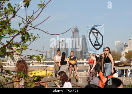 Young extinction rebellion protestors relaxing and chatting with a dramatic contrasting backdrop of skyscrapers and the group's flag - Stock Photo