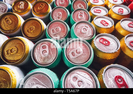 Metal cans of beer with ice cubes in mini refrigerator, close up. Lots of aluminum cans in the ice in the open fridge. Drops of water on a cold can of - Stock Photo
