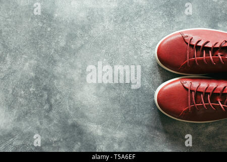 Woman fashion terracotta color shoes on gray stone background. Top view on red sneakers with copy space. - Stock Photo
