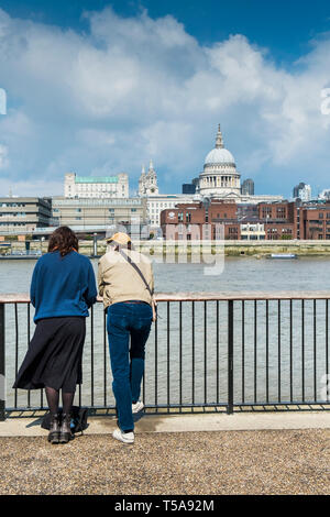 People leaning on railings overlooking the River Thames on the South Bank in London. - Stock Photo