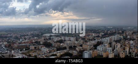 Aerial panoramic view of a residential neighborhood in a city during a cloudy sunrise. Taken in Netanya, Center District, Israel. - Stock Photo