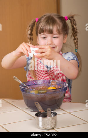Five year old girl breaking egg into a mixing bowl to become a chocolate bundt cake later.  (MR) - Stock Photo