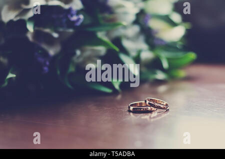 Beautiful wedding rings lie on a wooden surface against the background of a bouquet of flowers - Stock Photo