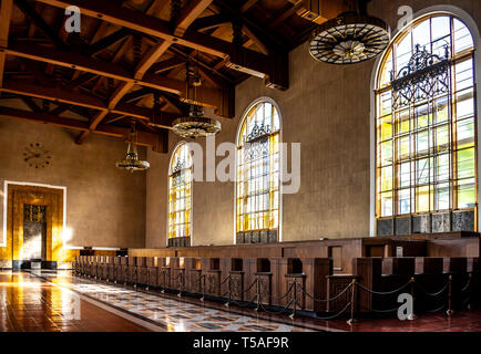 Light shining through Mission Revival windows, historic Union Station, Los Angeles, with Art Deco light fixtures hanging above former ticket counters. - Stock Photo