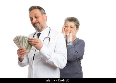 Greedy medic man counting dirty money with patient looking from behind and making worried expression and gesture touching face isolated on white - Stock Photo