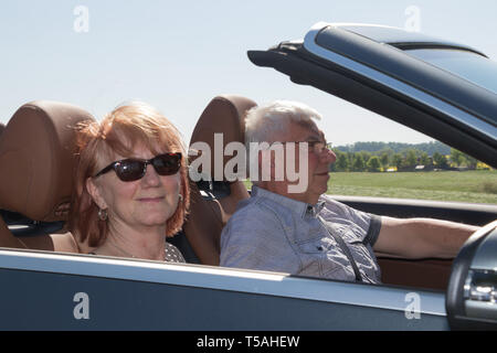 Happy senior couple with a luxury convertible car - Stock Photo