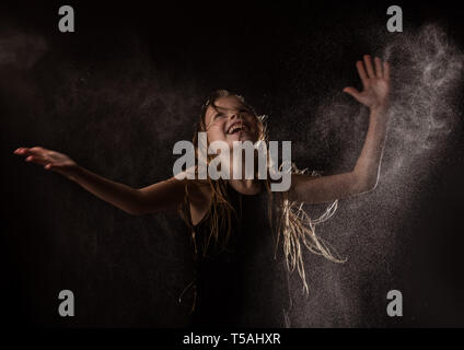 young girl with live emotions dancing under water drops. child splashing water on a dark background. - Stock Photo